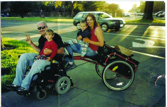 Danny and his wife, Katy, sit on his wheelchair with their two children.