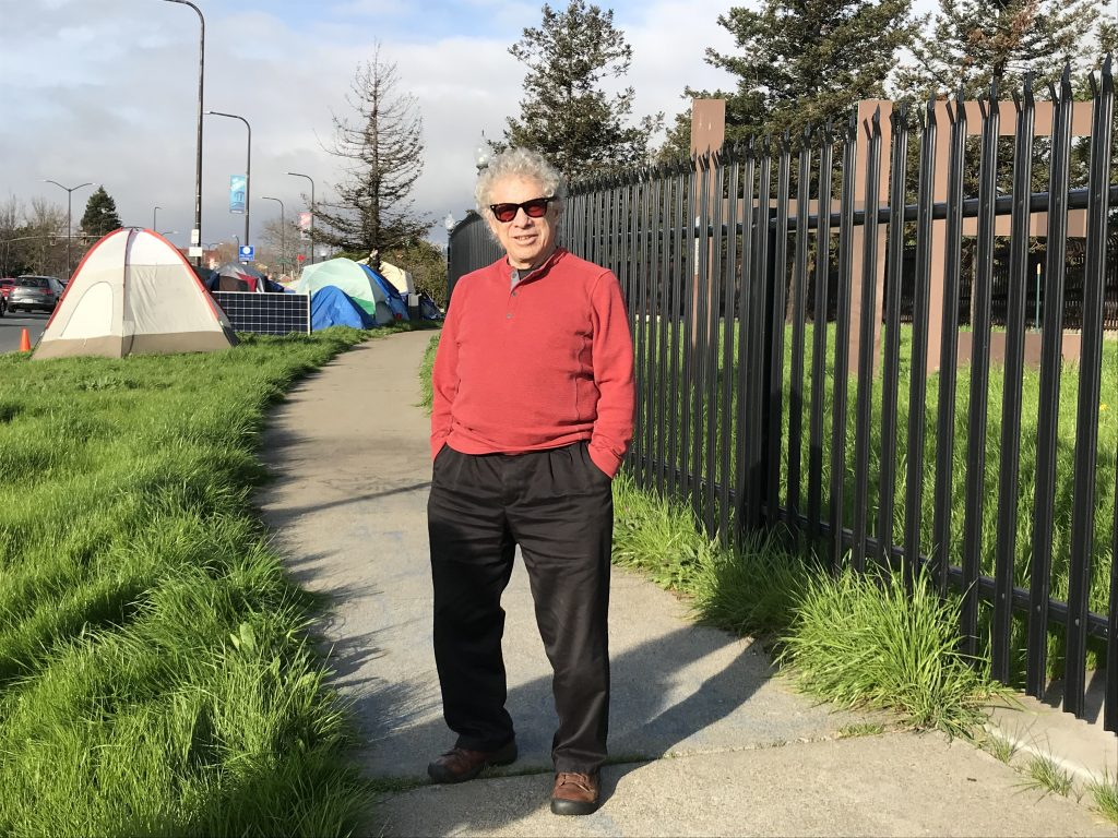 """Steve Gillman poses for a photo with the Here/There encampment, and part of the """"Here"""" sculpture, behind him."""