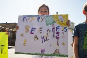 "A student from the Berkeley School holds a sign that reads, ""Every bee needs a hive."