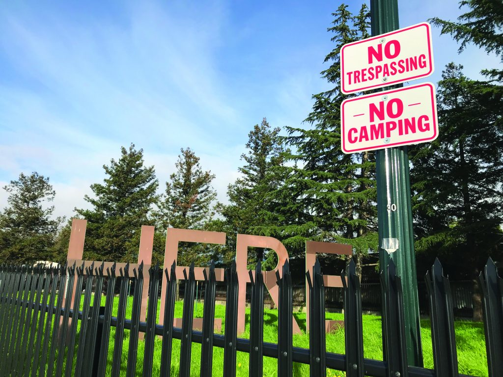 """The """"Here"""" portion of the sculpture. It's behind a fence and a sign that says """"no trespassing, no camping"""""""