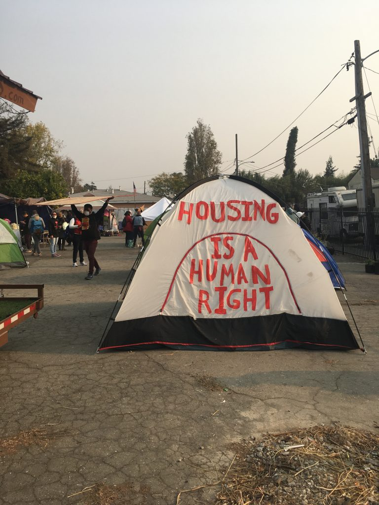 """Text on the side of a tent reads """"Housing is a human right."""""""