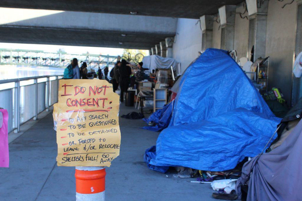 "A hand-written sign reading ""I do not consent"" is posted on a traffic cone in front of a homeless encampment. Residents created this sign as they braced themselves for the city to come through and evict them from underneath the 12th street bridge in Oakland."