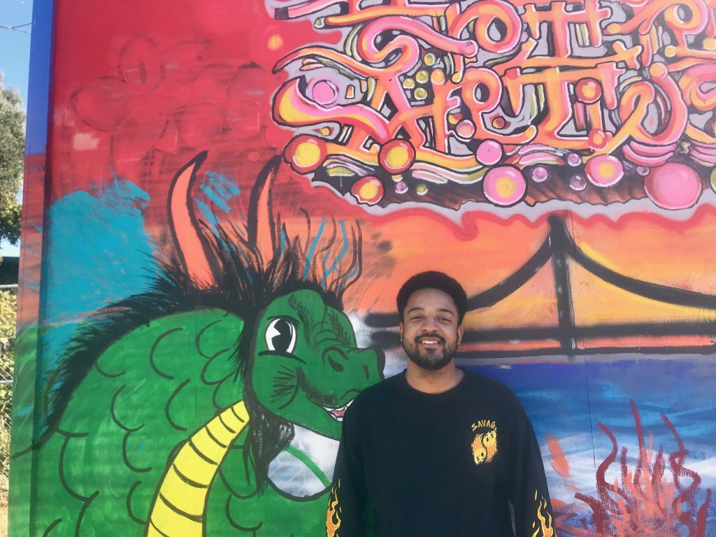 Reginald Gentry smiles for a photo in front of one of the tiny home murals.