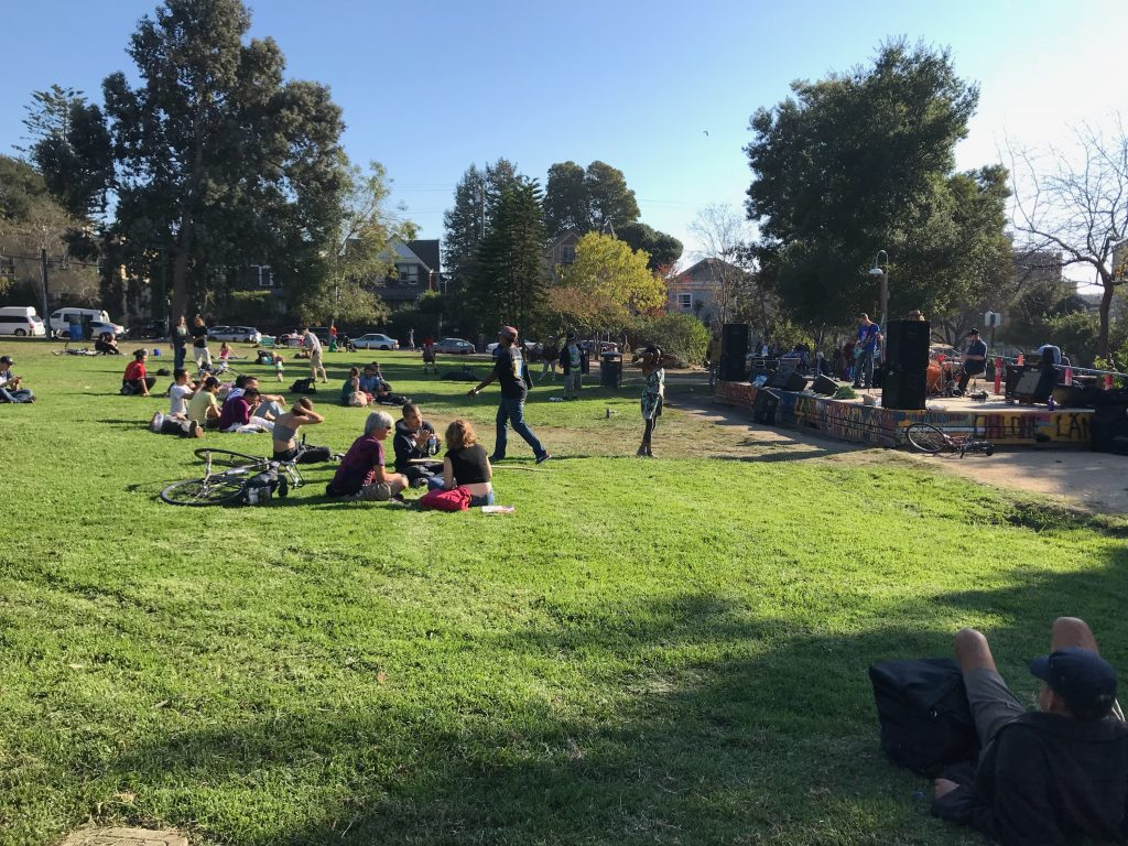 Concertgoers lounging in the grass at Berkeley's People's Park.
