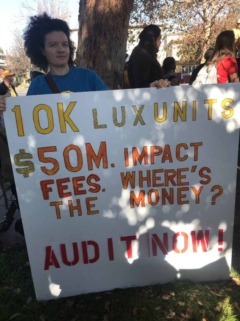 """Gloria Bruce holds sign that reads, """"10K Lux unites. $50 m impact fees. Where's the money? Audit now!"""""""