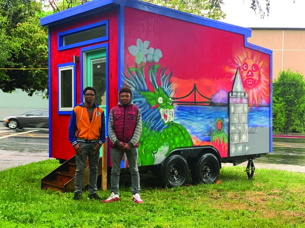 Youth Spirit Artworks leaders Jason Wilson and Zaire Caldwell (stand in front of a tiny home.