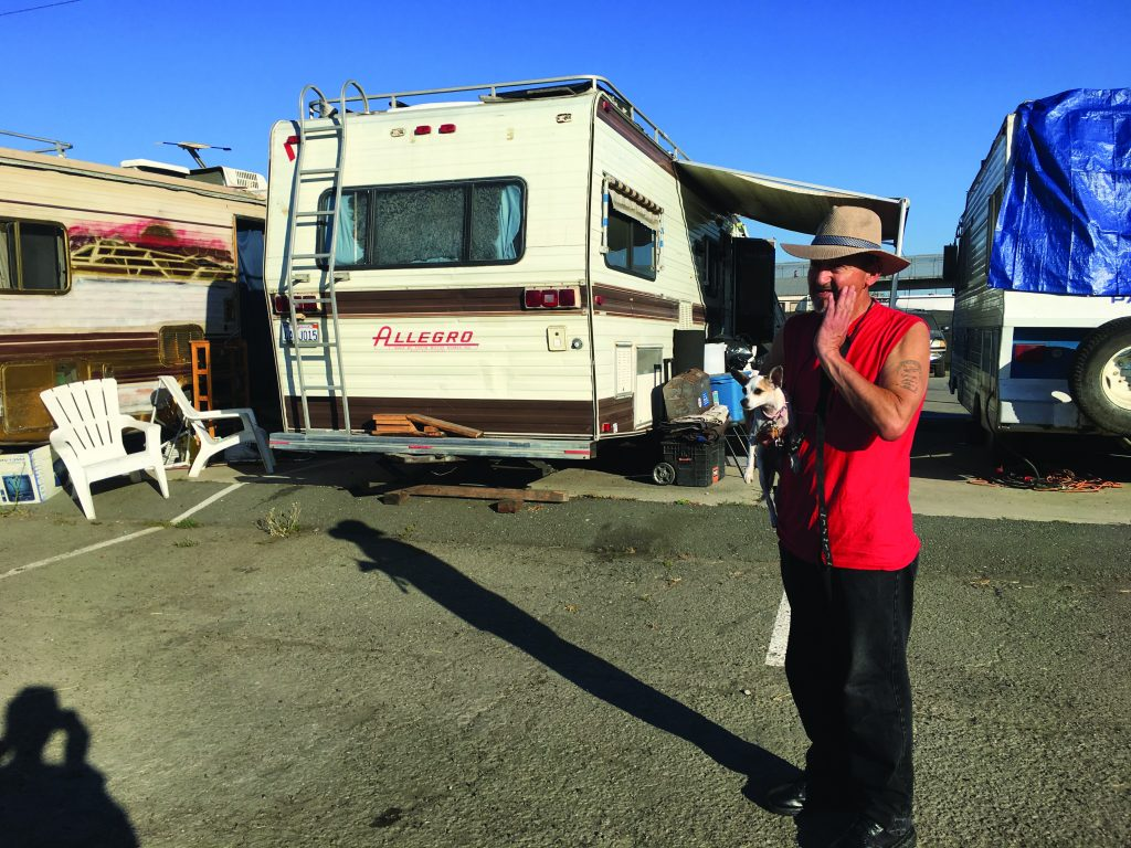 Jorge Peña holds his small dog in the parking space where his RV home is parked.