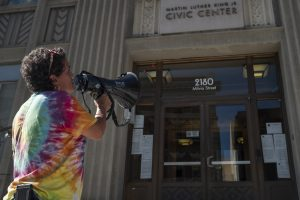 Andrea Henson speaks into a megaphone on the steps of Berkeley City Hall.