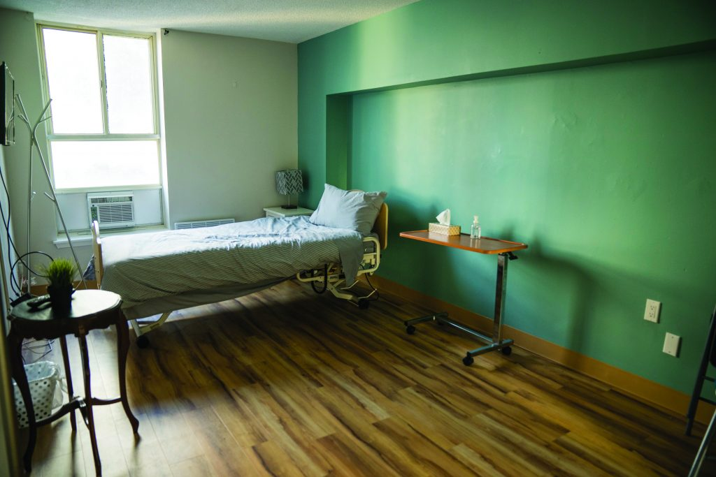 A hospital bed sits in a well lit room with light green walls.
