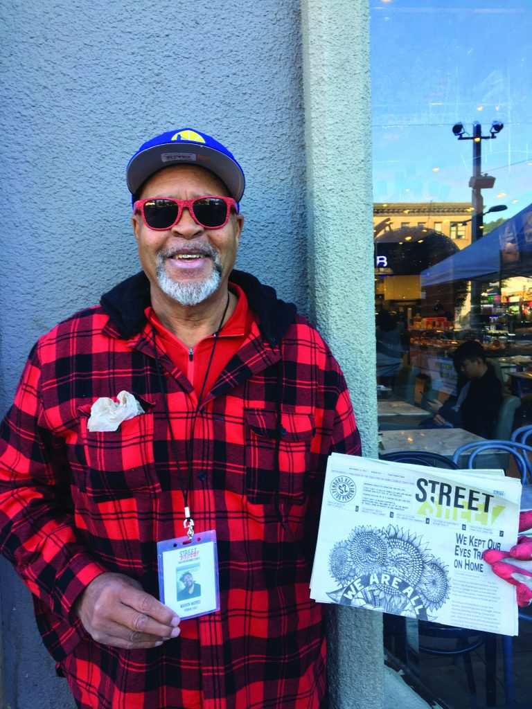 Marion Morris poses for a photo outside the Downtown Berkeley BART station, holing up a copy of Street Sheet.