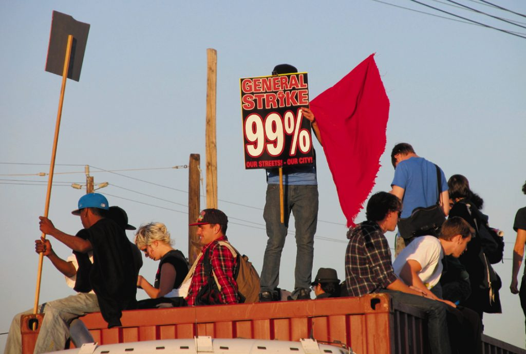 Demonstrators climbed on top of big rig trucks stranded when the Port of Oakland was shut down.