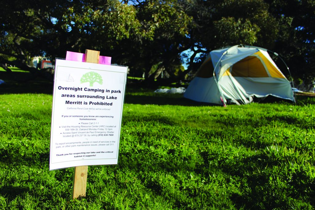 "A sign in the grass reads ""overnight camping in park areas surrounding Lake Merritt is prohibited."" Behind the sign, a yellow tent sits in the grass."
