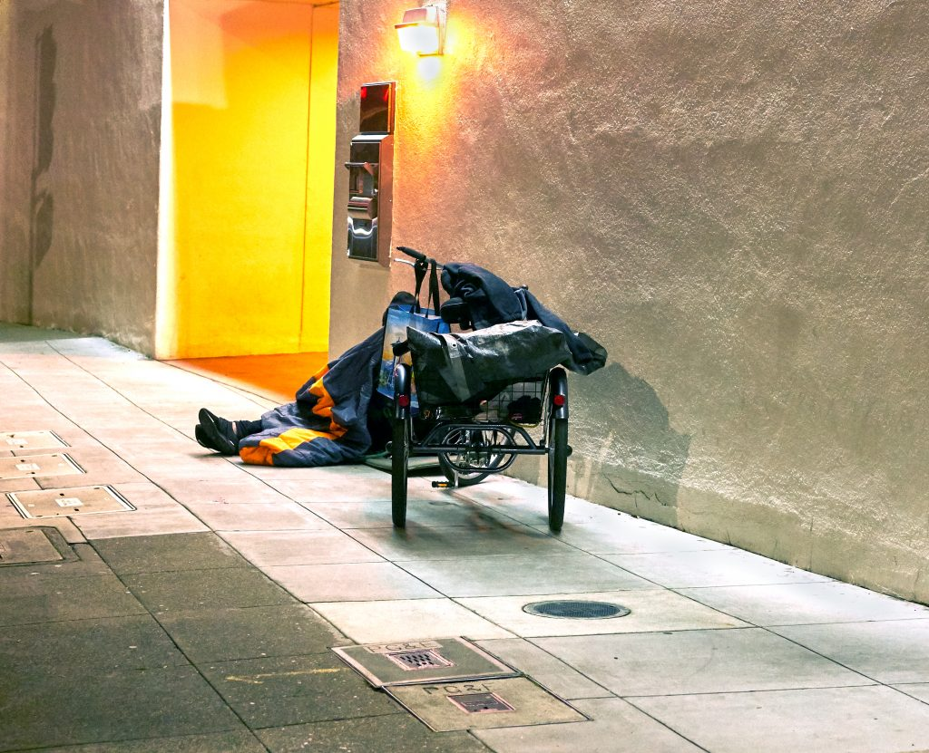 A homeless person sits on an empty Berkeley sidewalk. Only their feet are visible behind their cart.