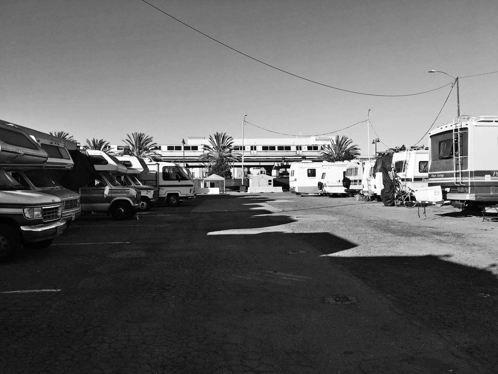 Black and white phono of an RV park cast in midday shadow