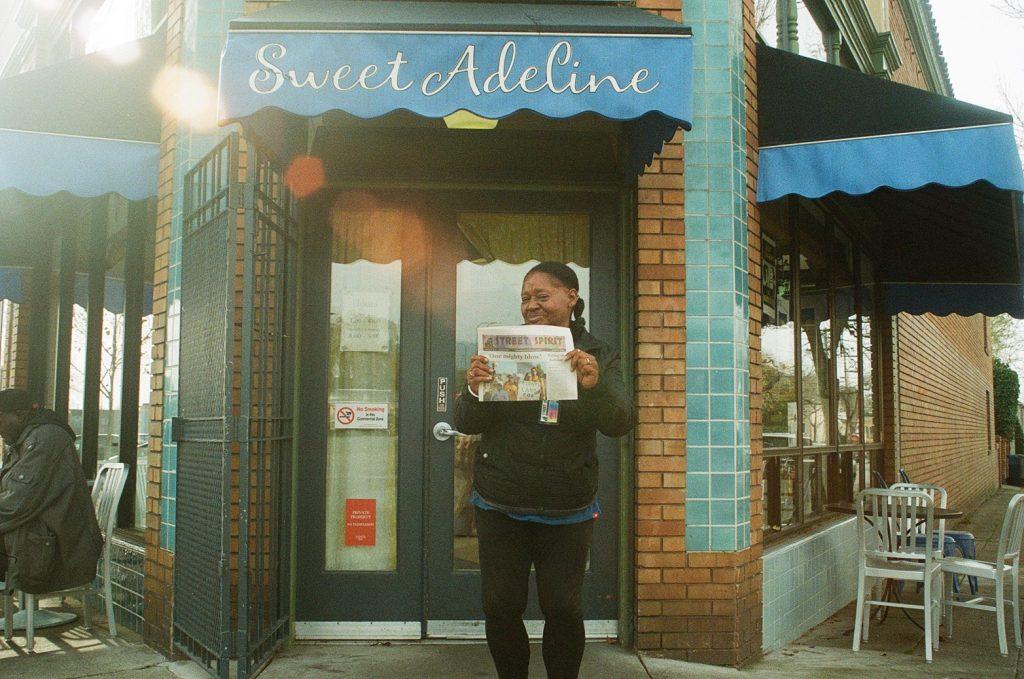 Photo of Rosalind Smith holding copy of Street Spirit.