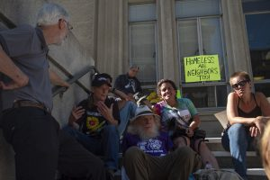 Protestors sit on the steps of Berkeley City Hall.