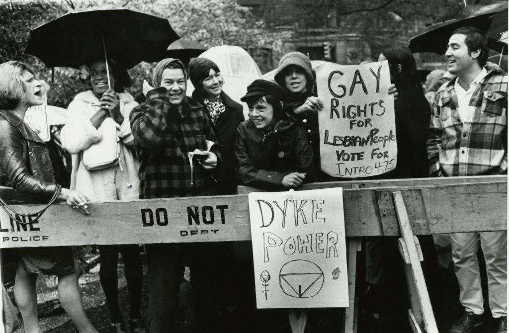 """A black and white photo of a group of people at a demonstration at City Hall, New York, 1973. They are holding umbrellas. A few people hold signs that read """"Dyke Power"""" and """"Gay rights for lesbian people vote for intro 475."""""""