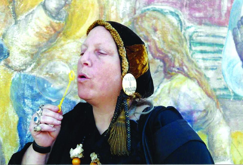 """Vinograd blows bubbles next her portrait in """"The History of People's Park"""" mural."""