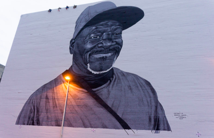 A large portrait of Derrick Hayes is painted on a wall in Downtown Oakland.