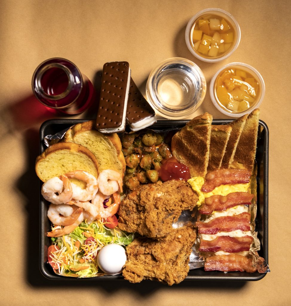 A tray full of lots of food: 5 strips of bacon, 2 slices of bread, scrambled eggs and grits for breakfast; 2 fried chicken breast tenderloins with ketchup and fried okra with hot sauce for lunch; 7 shrimp, garlic toast, tossed salad with a boiled egg for dinner; 2 ice cream sandwiches and 2 fruit cups for snacks; Water and fruit juice with most meals