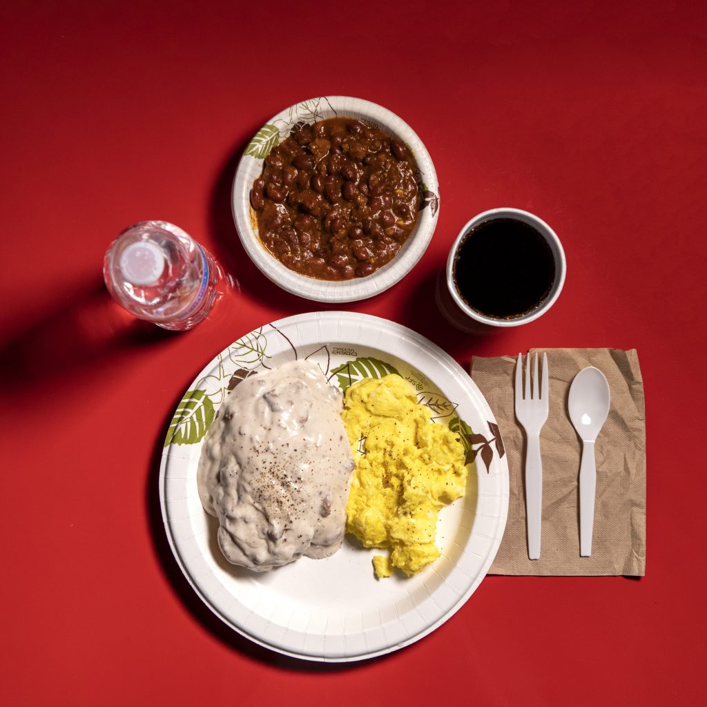 A paper plate of scrambled eggs, biscuits, and gravy, and a bowl of chili. Also, a bottle of water.