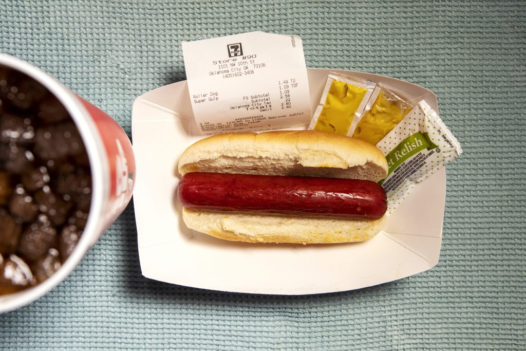 An arial view of a hot dog with two packets of mustard and a soda.