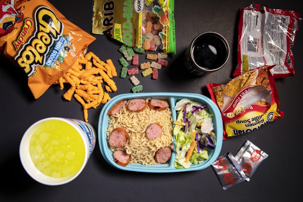 A container full of ramen noodles and sausage with salad. Also on the table are Cheetos, gummies, and a cup of Mountain Dew.
