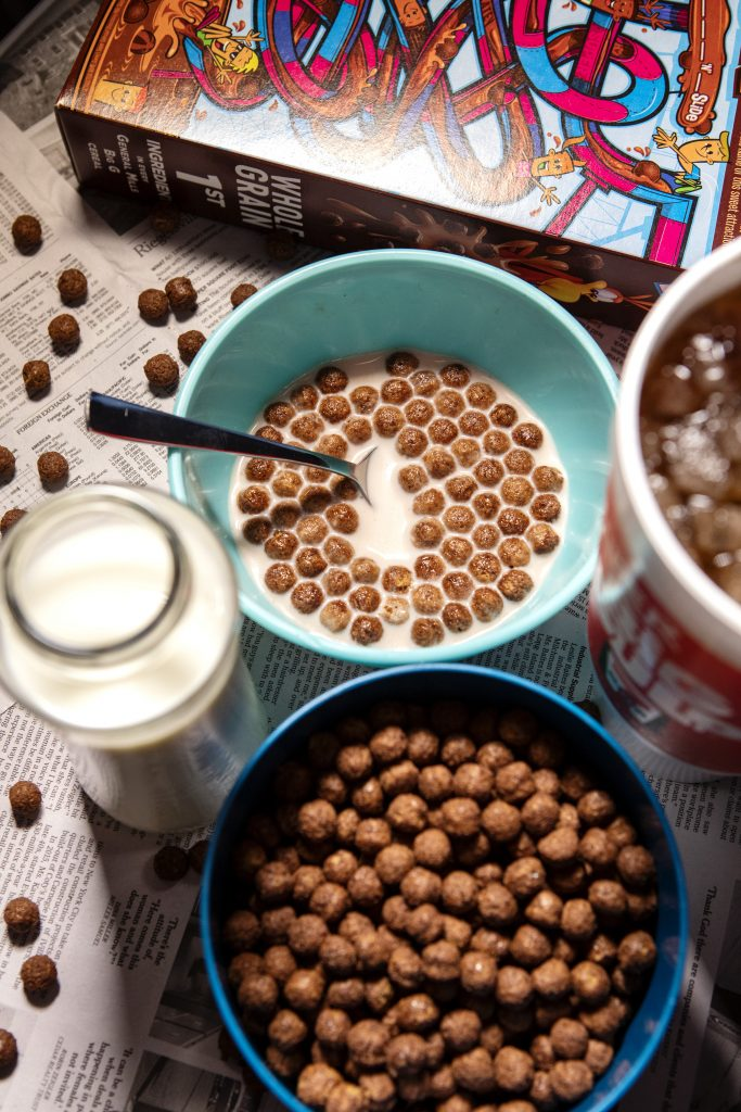 A bowl of Cocoa Puffs with milk and a soda on the side.