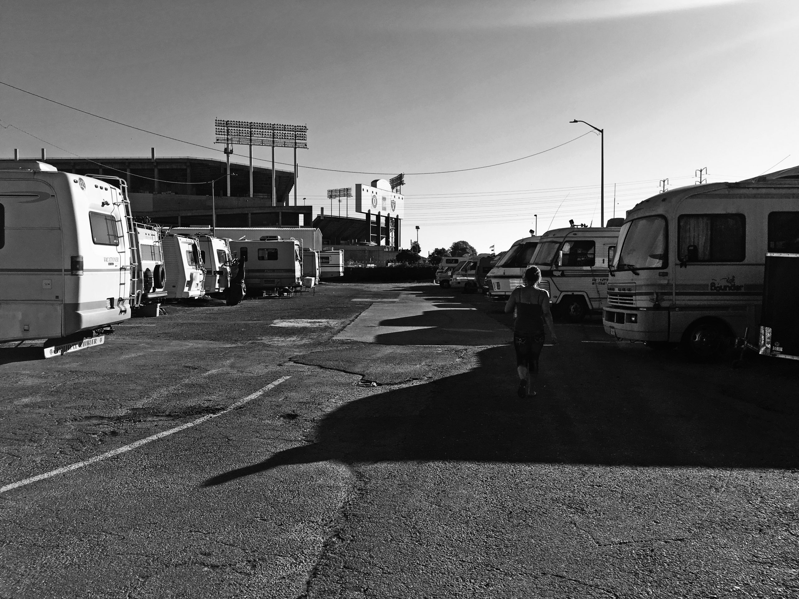 Black and white image of two rows of RVs. A solitary woman walks between them.