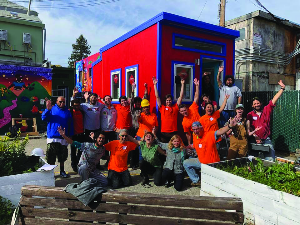 YSA leaders and volunteers celebrate the completion of one tiny home.
