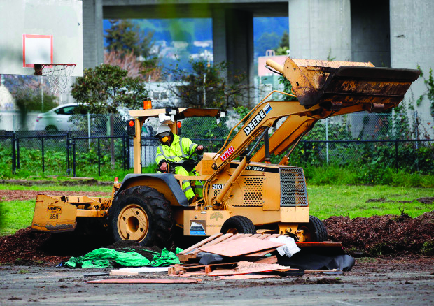 A public works employee on a tractor-like machine crushes wooden pallets and destroys the encampment.