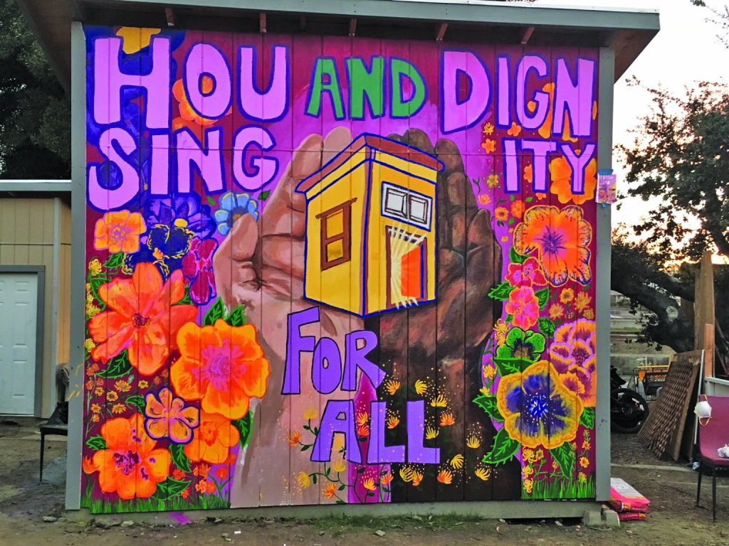 """A mural by artist Ellie Hwa Brumbaum adorns one The Village's latest guerilla tiny homes that reads, """"Housing and Dignity for all""""."""