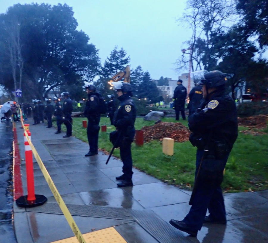 UC Police officers line up down Haste Street in front of People's Park while the tree cutting takes place.