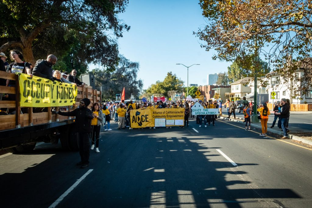 Photo of march. Alliance of Californians for Community Empowerment banner visible.