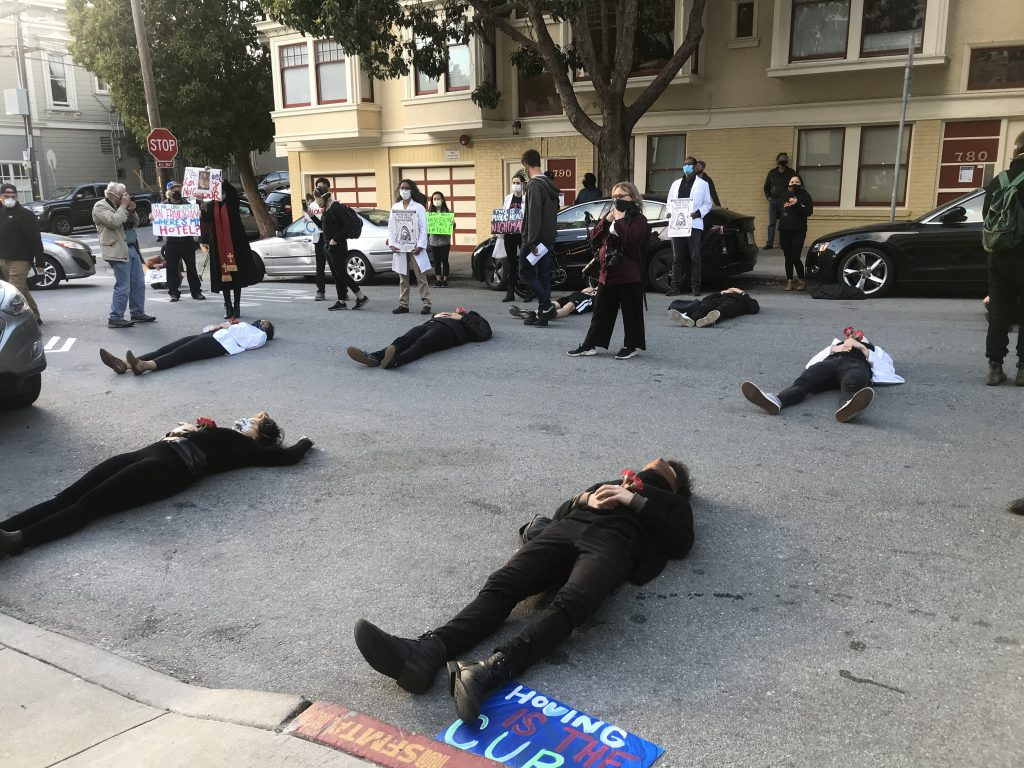 Protestors lie on the street in front of the mayor's house in San Francisco. They are wearing all black and holding red flowers.