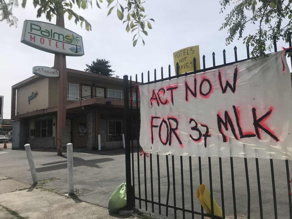 "A sign tied to the fence of the Palms Motel reads ""Act now for 37 MLK"". The Palms Motel sign stands in the background."