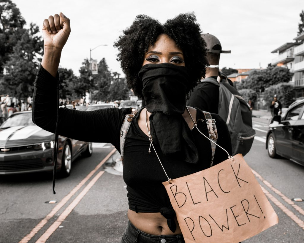 "A black woman wearing all black and a face mask holds up the fist of black power. She has blue eyeshadow on, and holds a cardboard sign that says ""Black power!"""