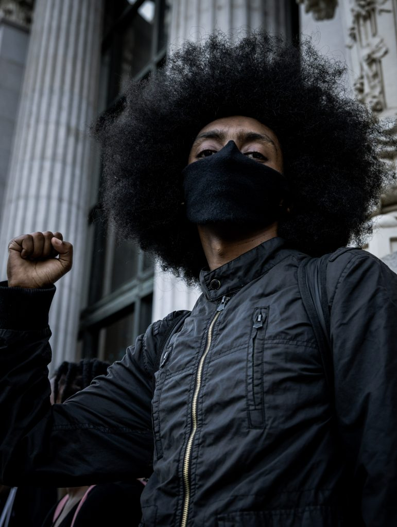 A Black man wearing a large afro and a black face mask holds up the fist of black power in front of Oakland City Hall.