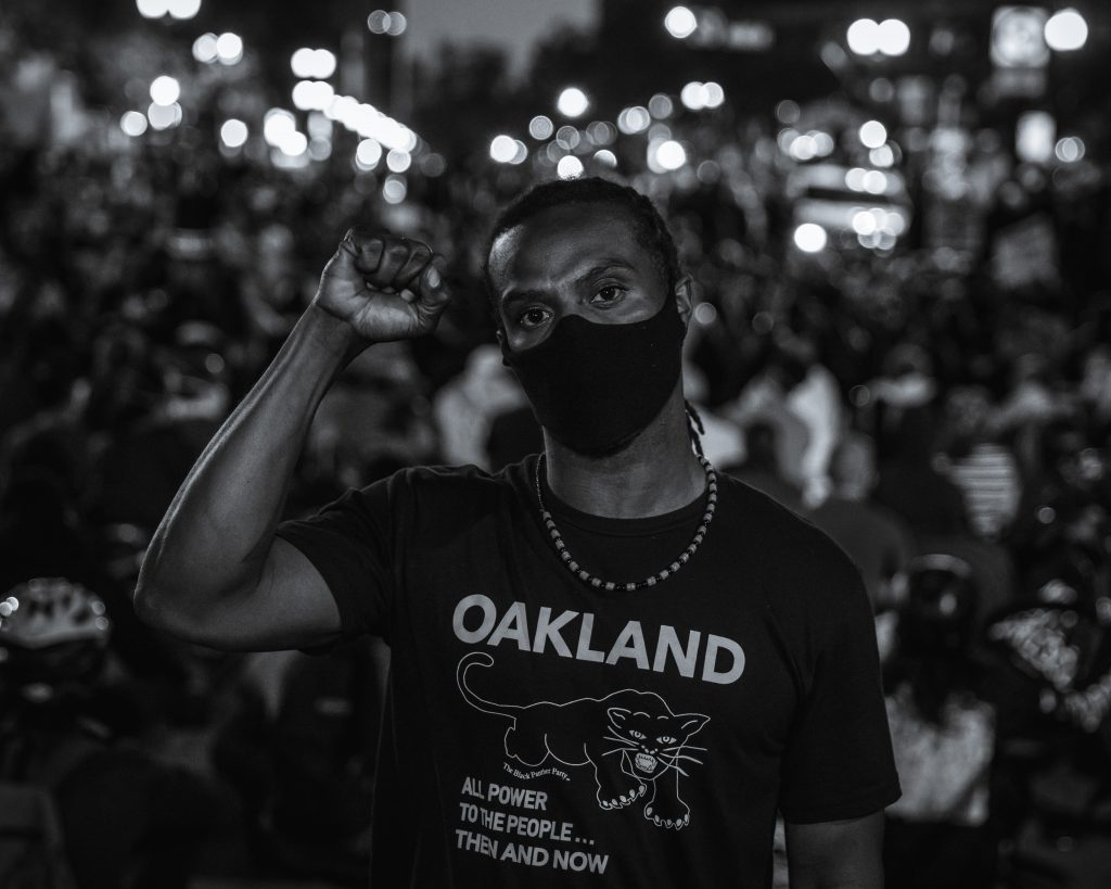 "A Black man holds up the fist of black power in front of a blur of protestors and light behind him. The image is in black and white. He is wearing a shirt that says ""Oakland"" on it, and has a photo of a black panther. Underneath, it says ""all power to the people...then and now"""