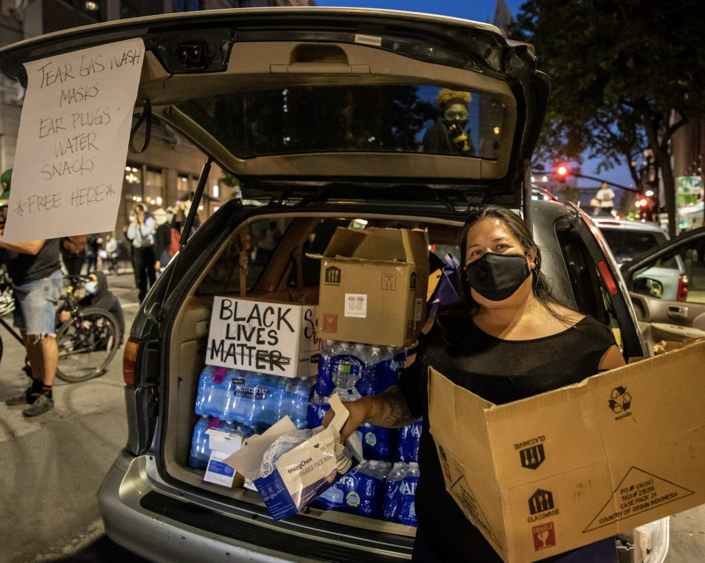"A woman wearing a face mask stands by the trunk of her car, which is open. Her trunk is full of water bottles. A sign on her open trunk reads ""tear gash wash, masks, ear plugs, water, snacks, free here."" A sign in her trunk reads ""Black lives matter."""
