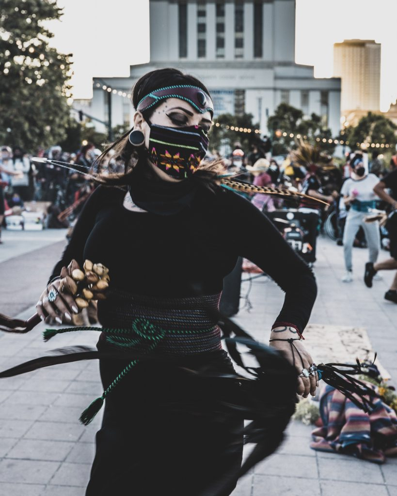 Action shot of a woman in traditional Aztec clothing dancing in front of Oakland City Hall. She is wearing all black, and there are a few bright pops of color in her outfit. She is holding a shaker in her hand and looking downward.