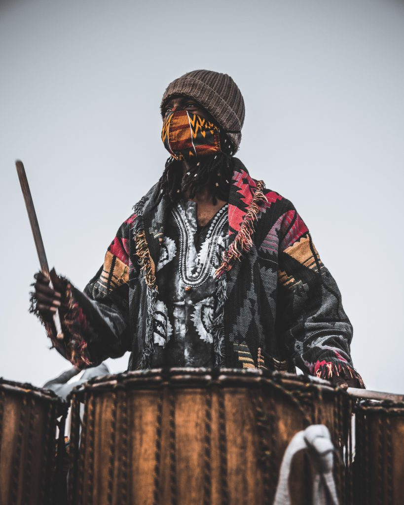 A Black drummer in wearing colorful tribal patterns and a colorful tribal face mask holds up one drum stick, as if about to hit his drum. He looks off into the distance.
