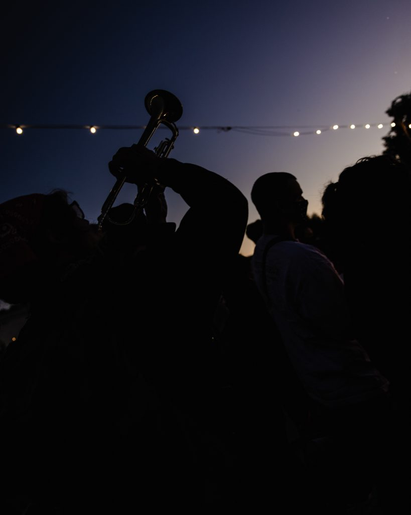 A night time image showcasing the silhouette of a trumpet player in the foreground, playing his trumpet up into the air. Behind him you can see the string lights of Lake Merritt, and the last rays of the sunset.