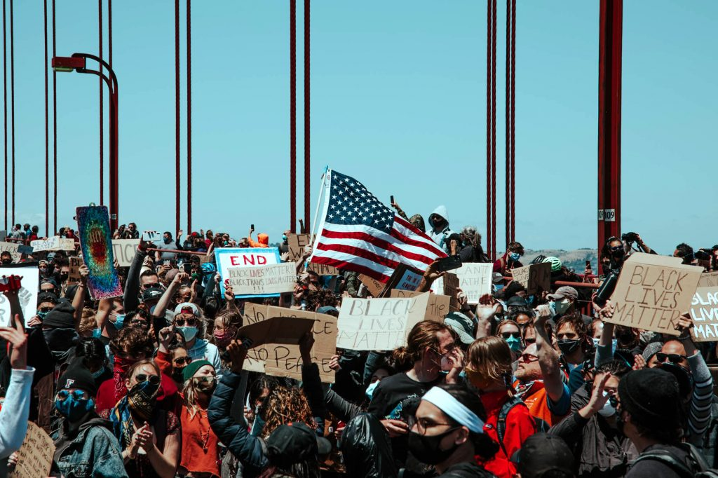 Protesters raise the American flag on the Golden Gate Bridge. Tons of people fill the frame, holding signs and standing on the roadway.