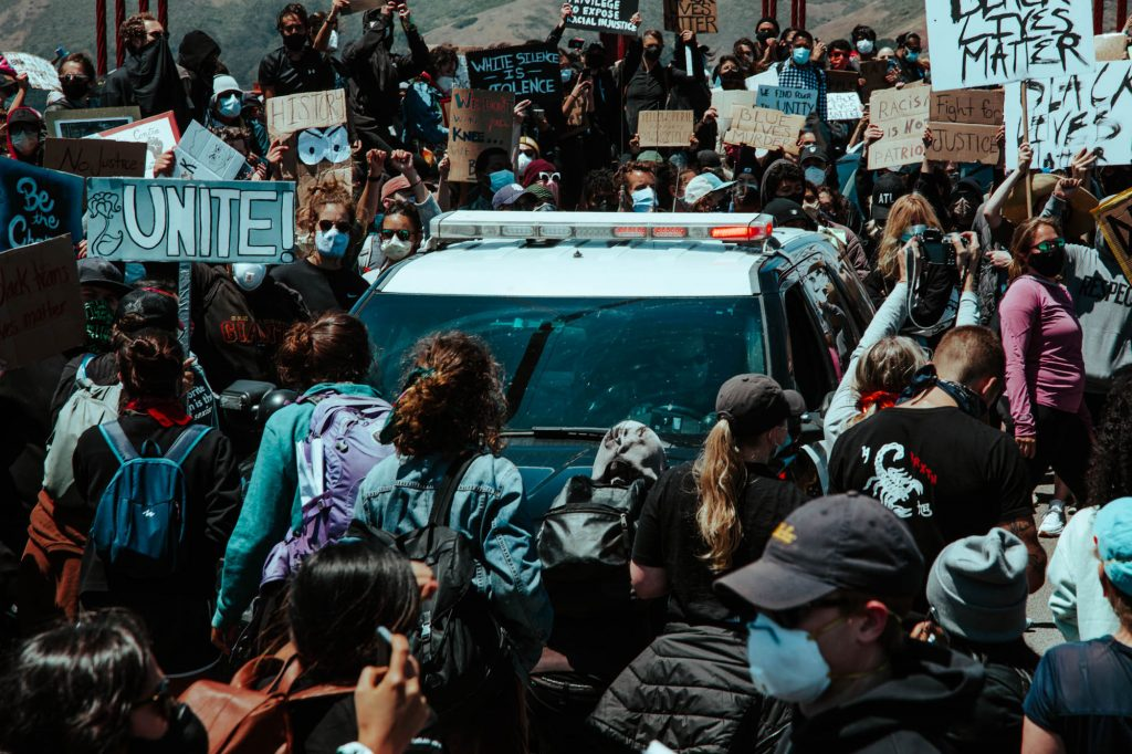 A dense throng of protestors encircle a police car on the Golden Gate Bridge. In the background, the bridge's red cables can be seen.