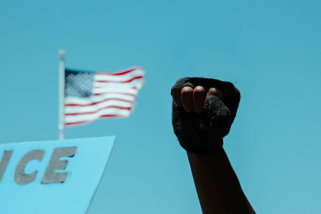 A black protester raises their fist at the San Francisco entrance to the Golden Gate Bridge. In the photo, only the fist can be seen jutting up into the clear blue sky. An American flag flies in the background.