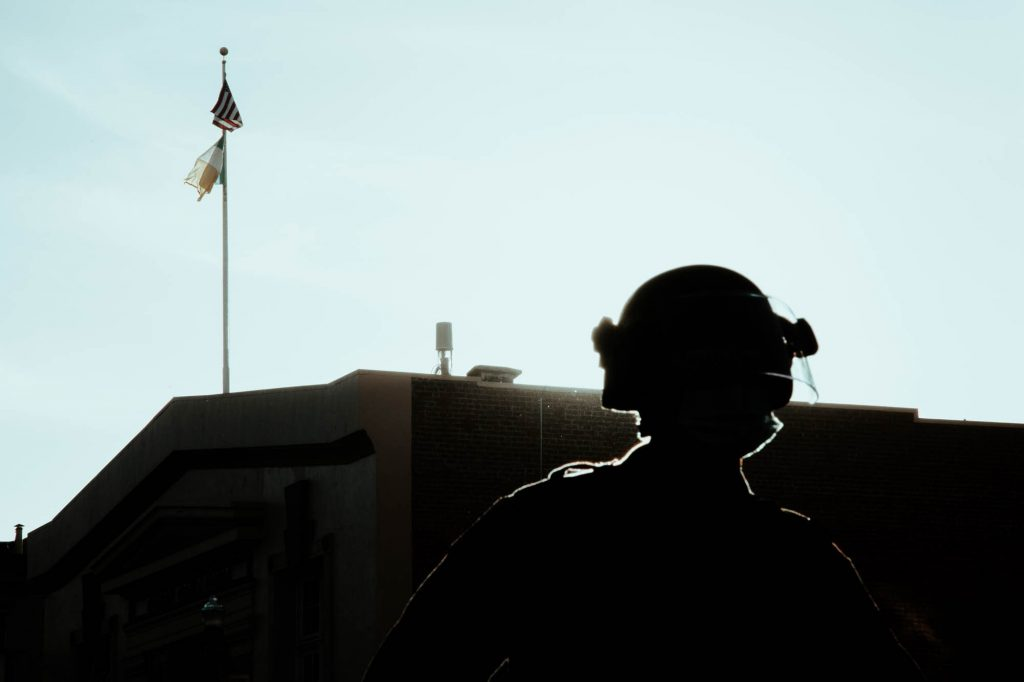 The silhouette of a police officer can be seen standing on San Francisco's 17th street. The sun shines behind them.