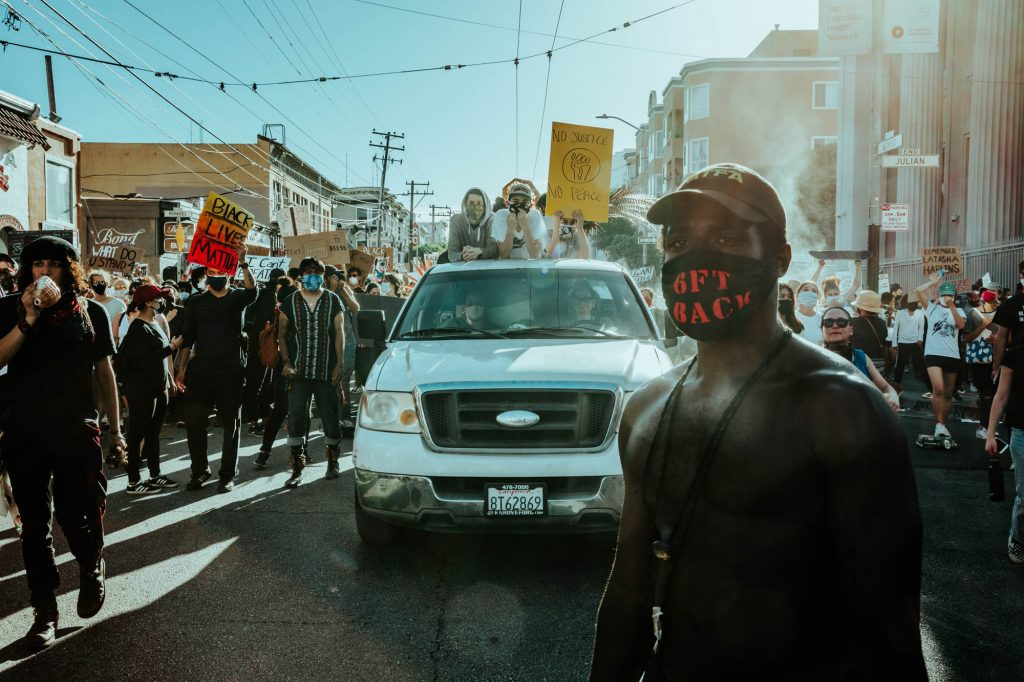 "Protestors march down San Francisco's 16th street. In the foreground, a protestor wears a mask that says ""six feet back"" in red letters. In the background, three protestors stick their heads out of the sunroof of a car, holding signs. All around them, protestors march and carry signs."