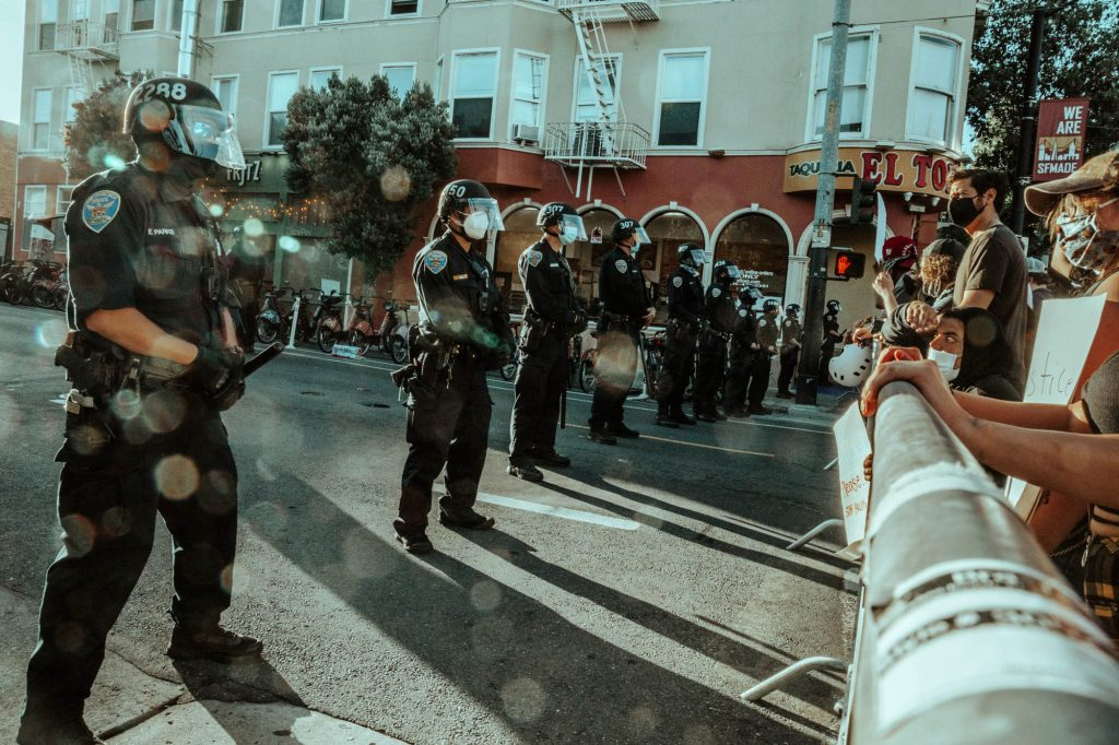 A line of police stand behind a barrier in front of protesters at the Mission police station.