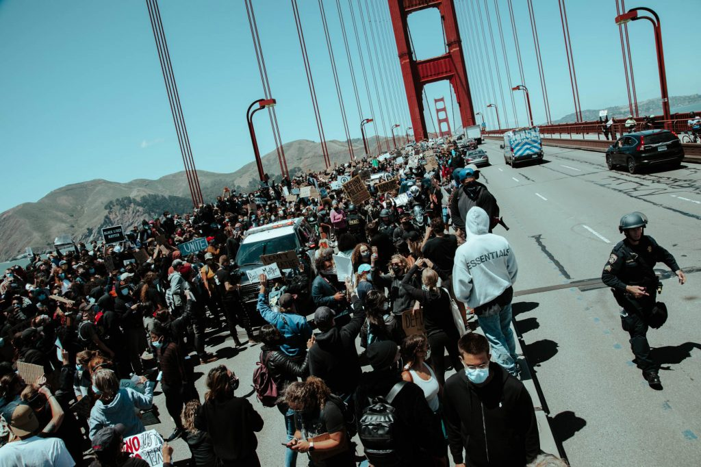 A dense group of protestors stand in the southbound lanes of the golden gate bridge. The northbound lanes remain free of protestors, for now.